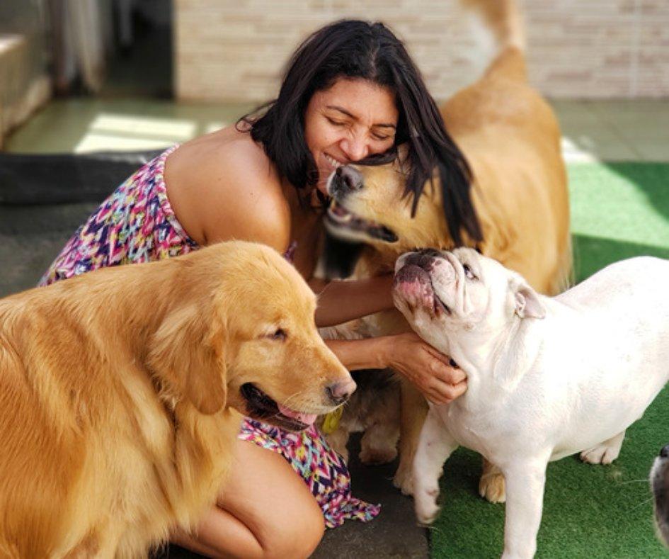 mulher abraçando cachorro em hotel pet